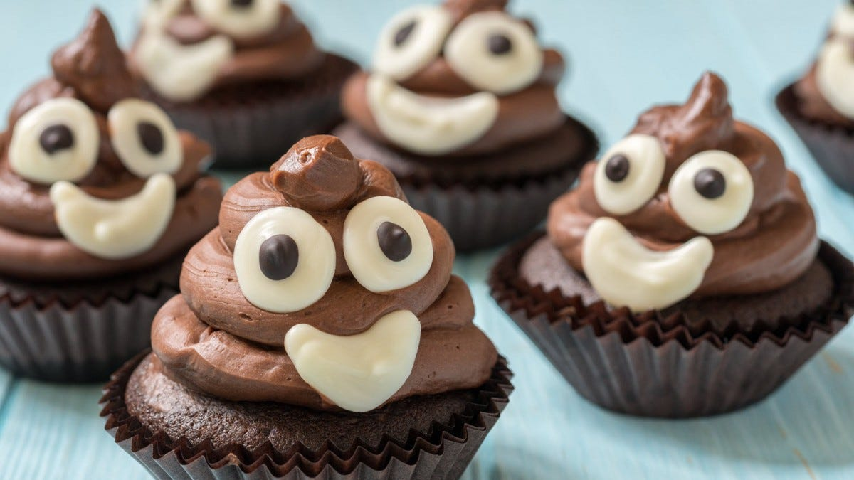 Four cupcakes with frosting that resemble poop emoji.