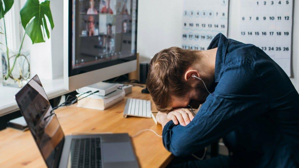 man snoozes through a boring video meeting