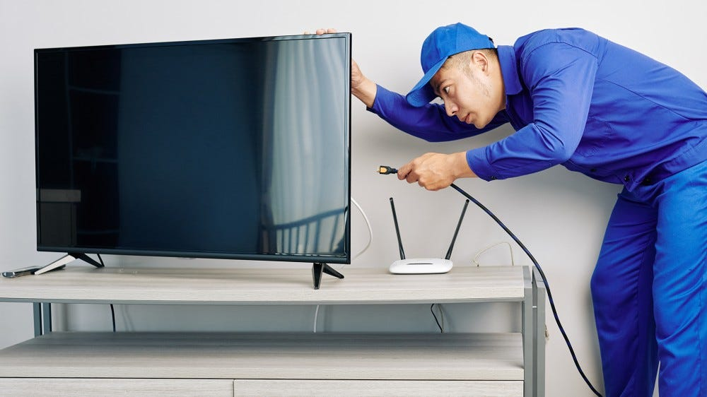A cable technician plugging a coaxial cable into the back of a flatscreen TV.