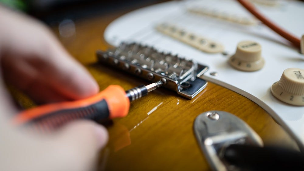 A photo of someone adjusting the intonation on their guitar.