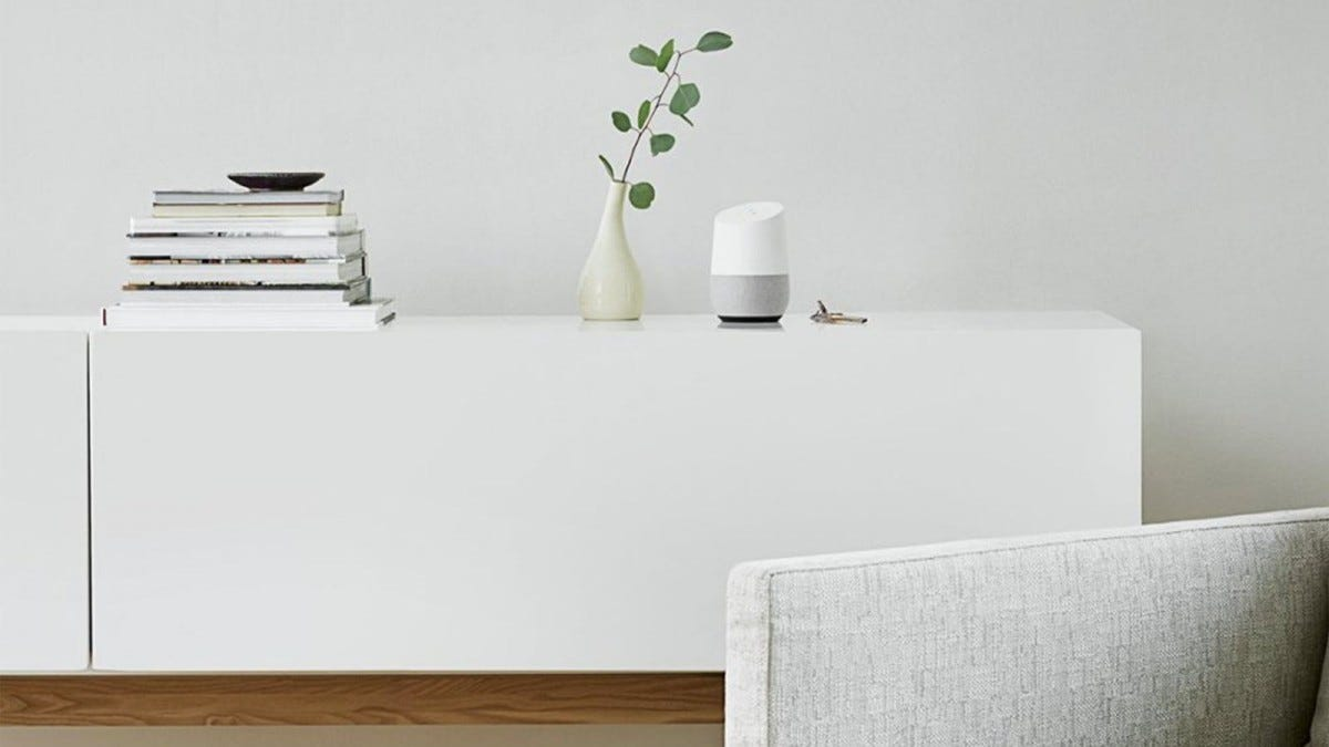 A Google Home Smart Speaker on a tv stand with a plant.