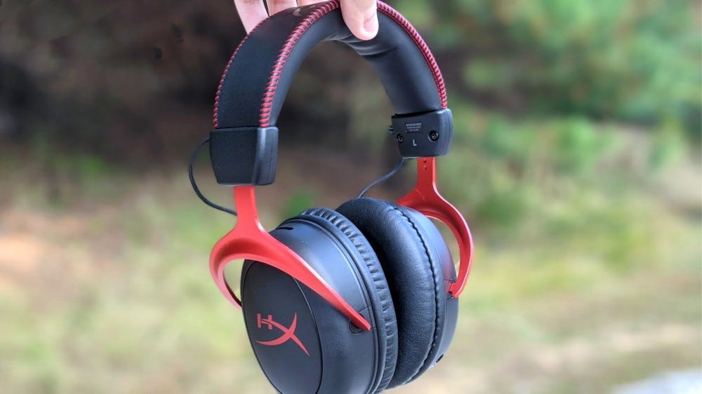 HyperX Cloud II Wireless Gaming Headset help up against forest backdrop