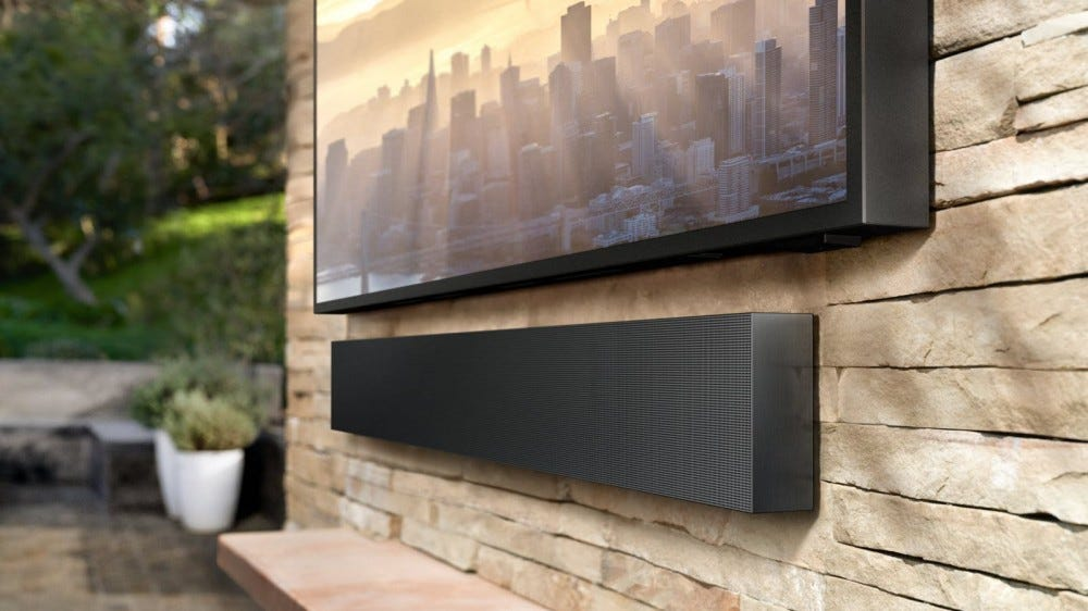 A soundbar mounted to a wall outside.