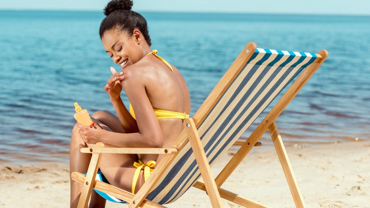 A woman at the beach applying gel sunscreen.