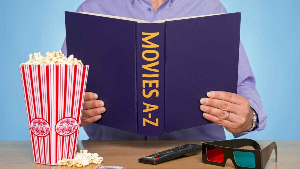 "A man holding a book titled ""Movies A-Z"" and some popcorn"