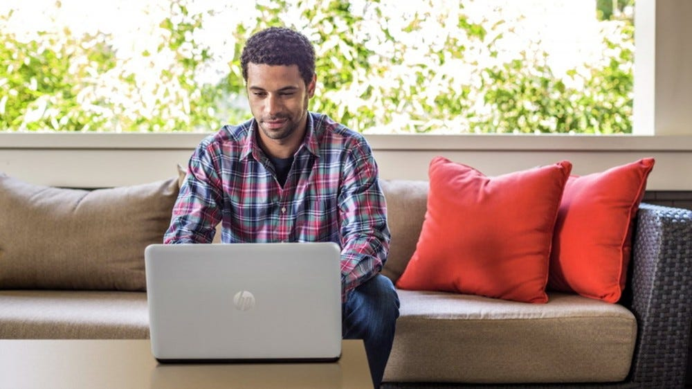 A man looking at an HP EliteBook laptop.