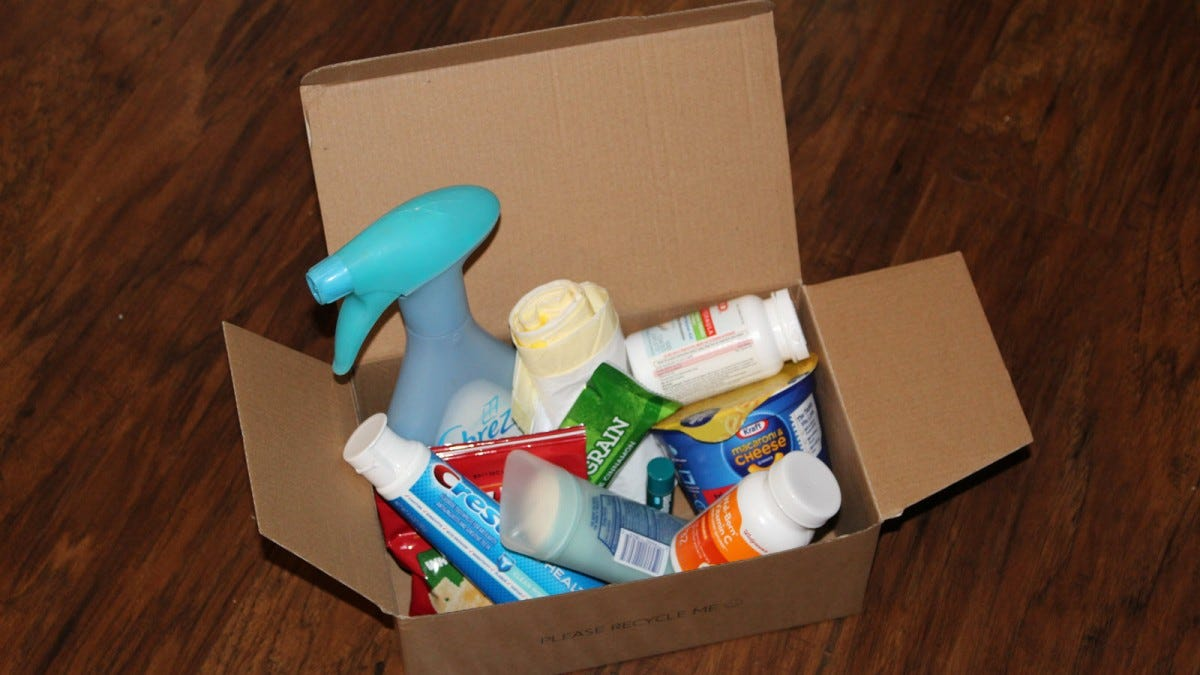 A box filled with toothpaste, snacks, medicines, trash bags, and cleaning supplies.