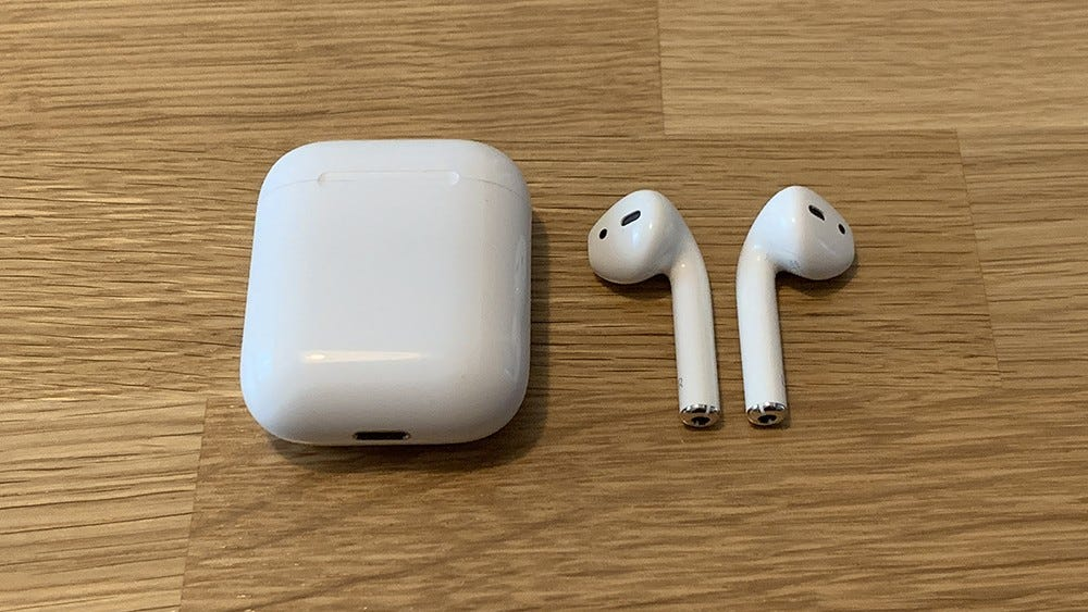 Apple AirPods, beside their case, on a wooden table