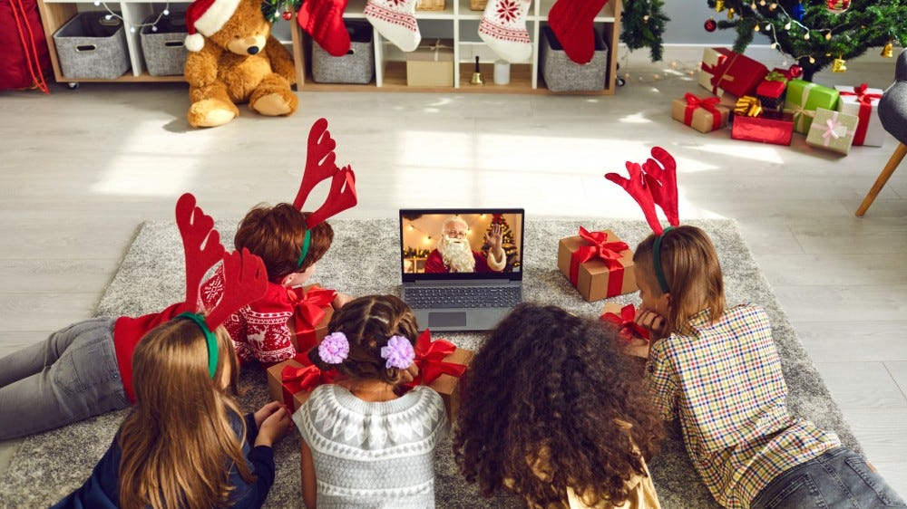 A group of children watch a video chat with Santa using a laptop in a festively decorated house