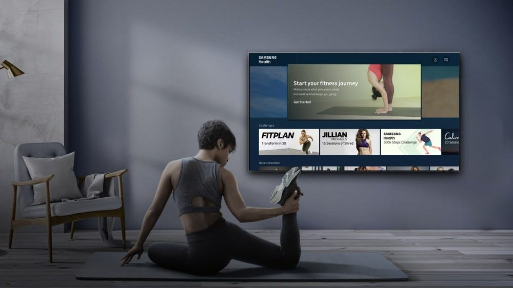 A woman stretching by a Samsung TV running the Health app