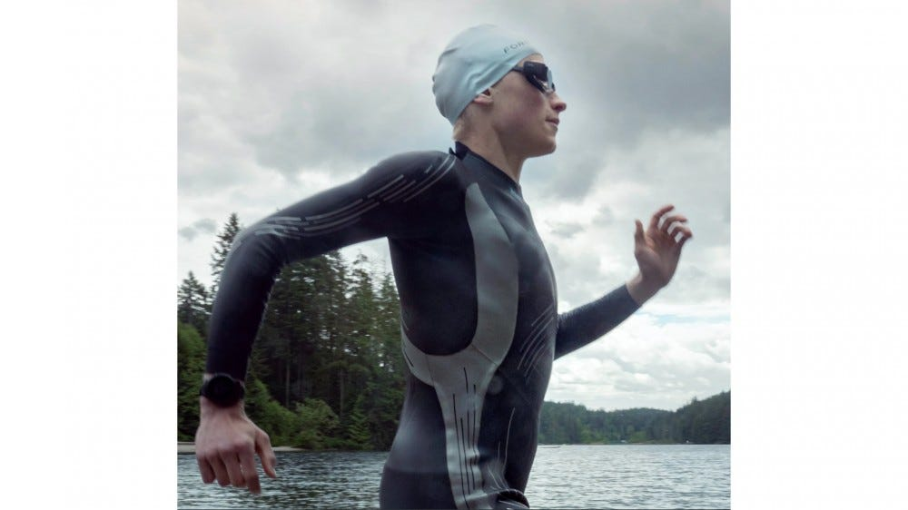 Swimmer athlete wearing bodysuit and FORM AR smart goggles about to jump into water for a swim
