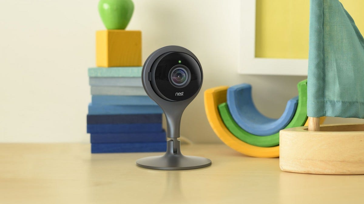 A Nest security camera on a coffee table surrounded by toys.