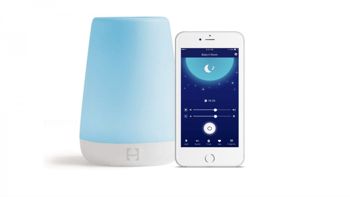 "The Hatch Baby Rest Sound Machine next to a smartphone showing ""Baby's Room on the app."