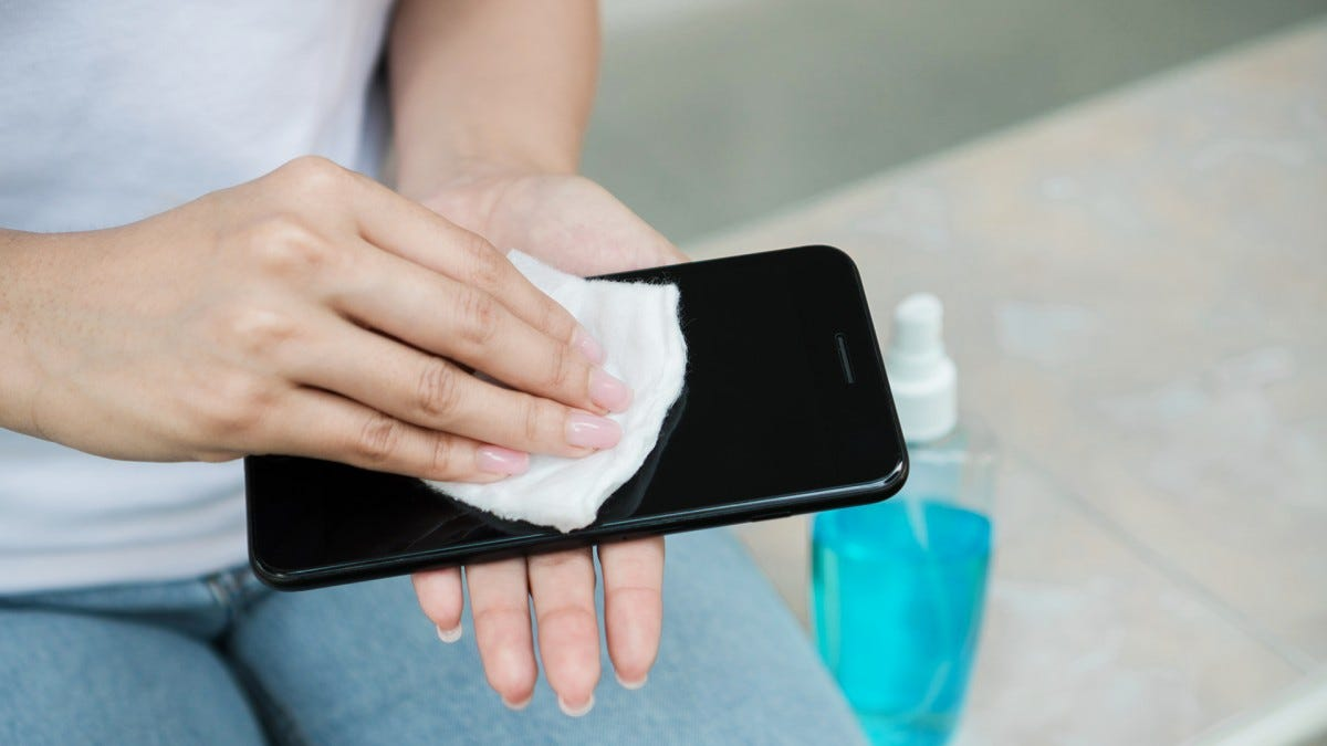 A photo of a woman cleaning her phone.