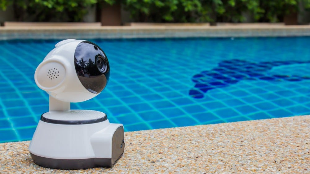 A small security camera by a pool