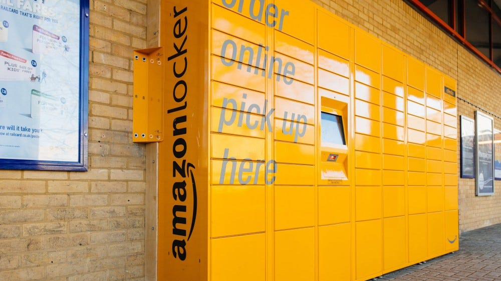 A yellow Amazon Locker system along a brick wall.