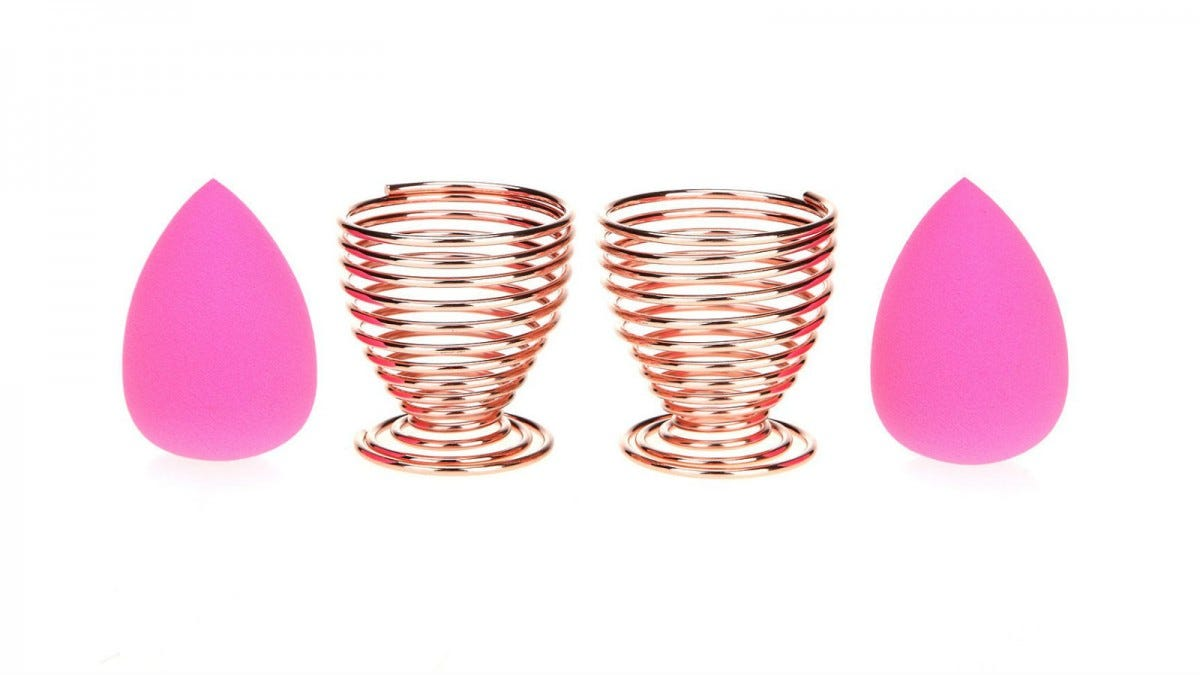Two rose gold LanMa Beauty Sponge Blender Holders and two pink makeup sponges.