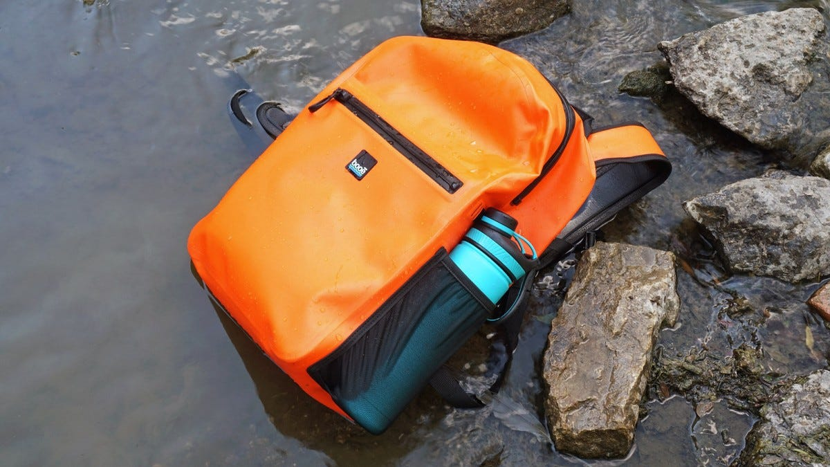 A Booē Hybrid 20 backpack lying in a stream.