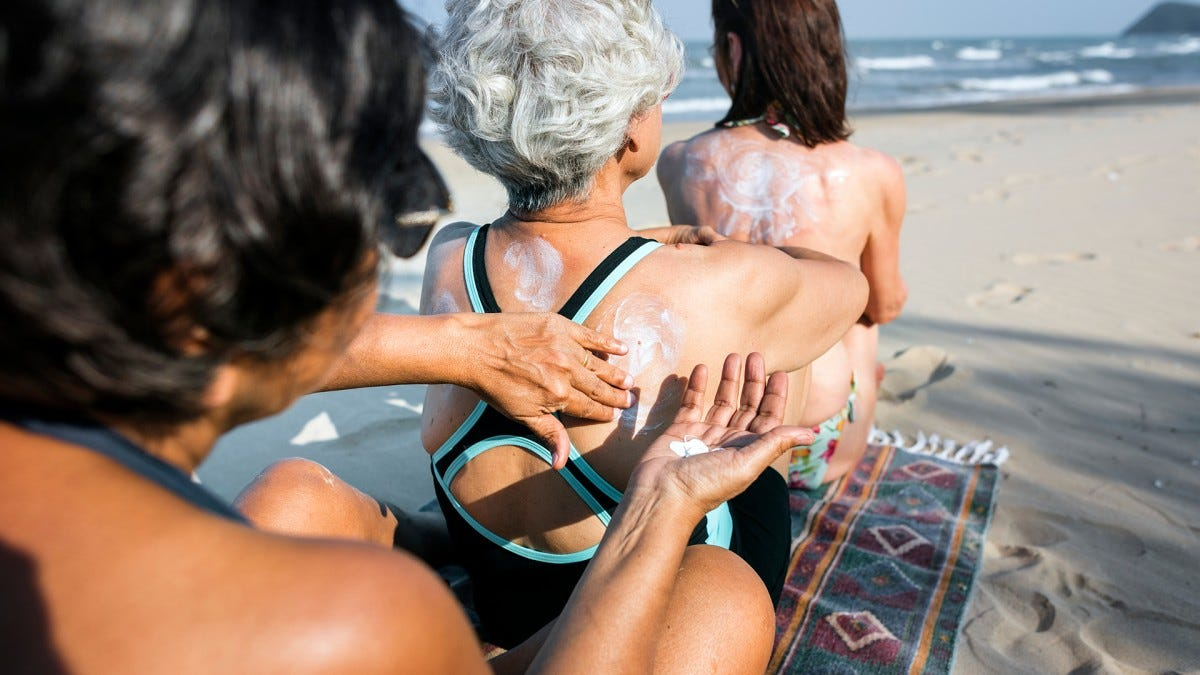 Three women at the beach applying sunscreen to each other's backs.