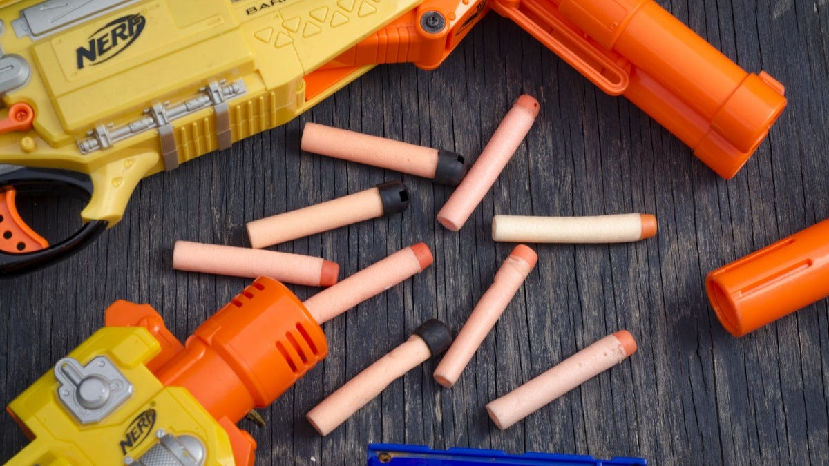 A pile of foam darts sitting in the middle of several Nerf guns.