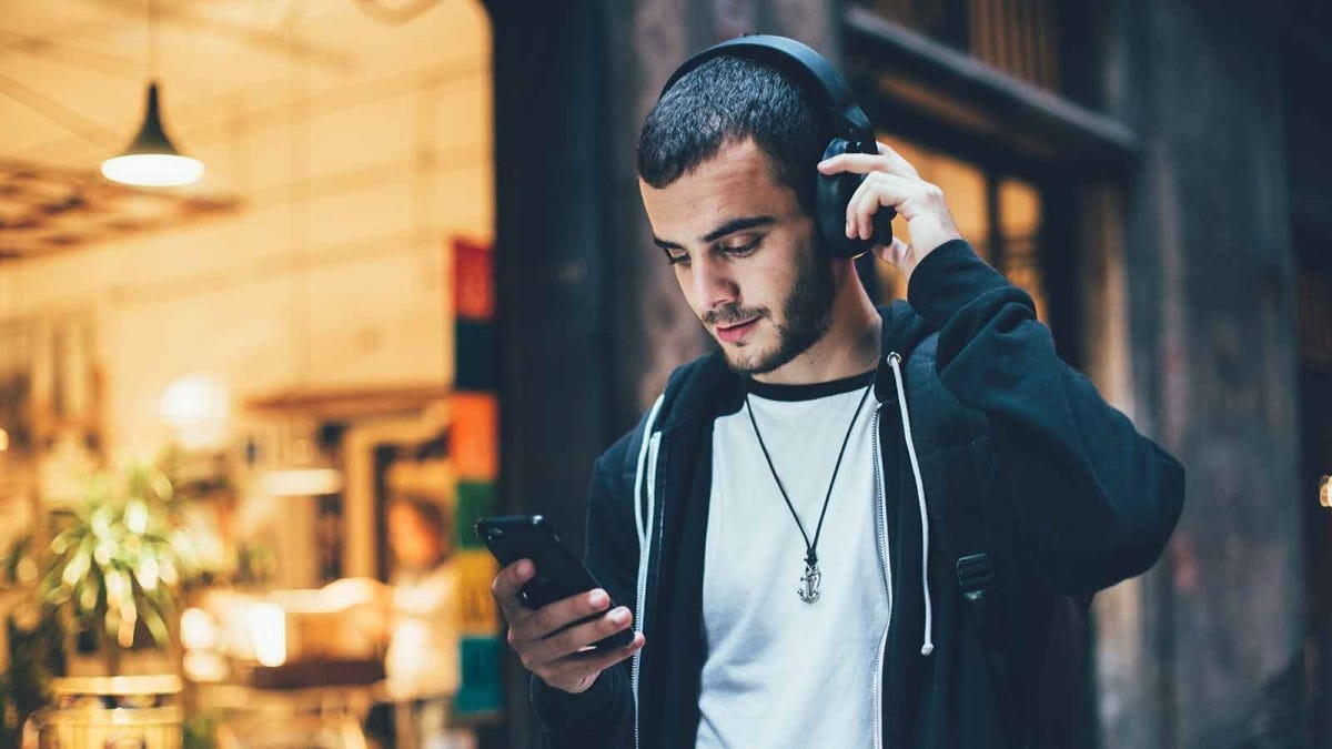 Man listening to music on the street using noise-canceling headphones