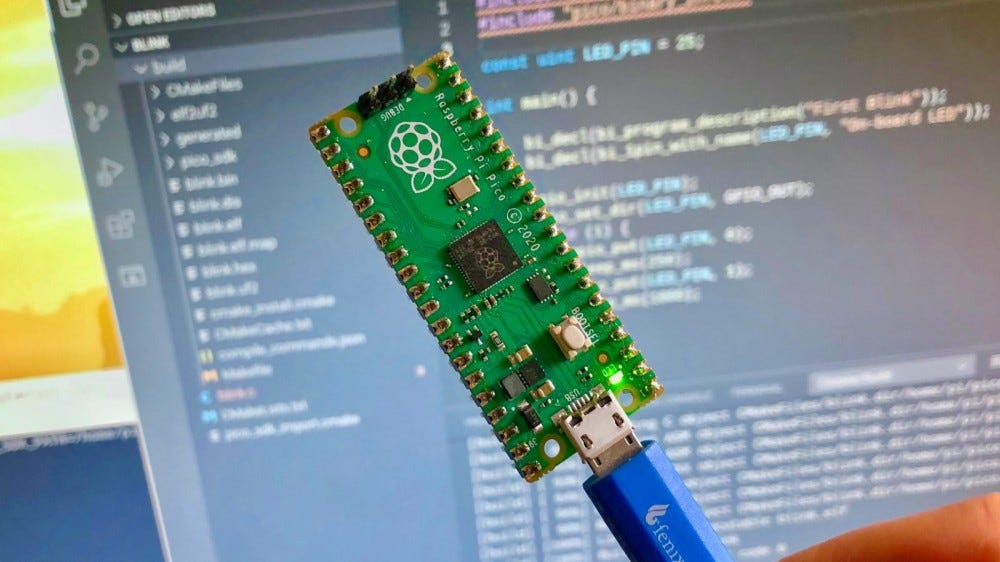 A photo of the Raspberry Pi Pico microcontroller with a USB cable.