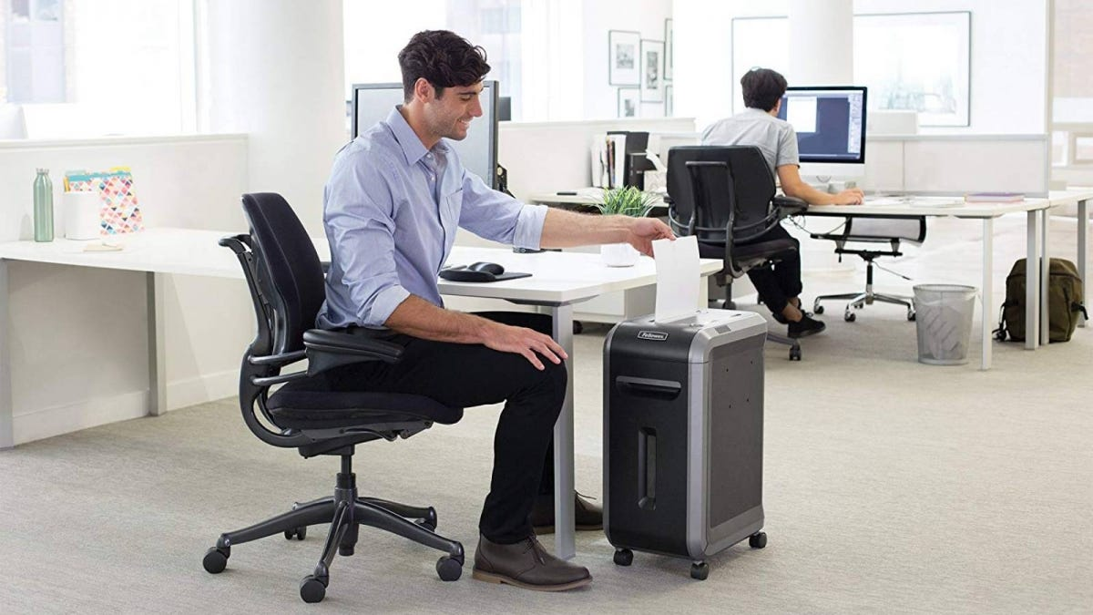 Man at his desk in an office using Fellowes Powershred Paper shredder.
