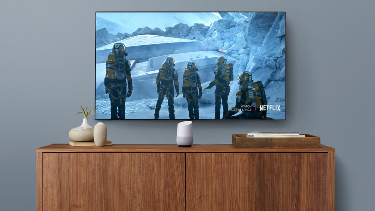 A Google Home on a TV stand under a TV showing Netflix.