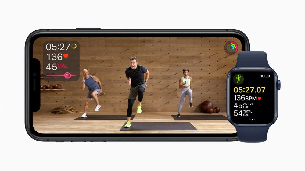 An Apple Watch next to an iPhone with an on-screen trainer and on-screen Apple Watch statistics.