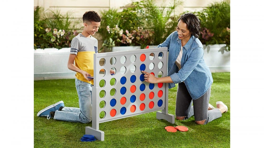 Giant connect four outdoor set with adult and kid playing together