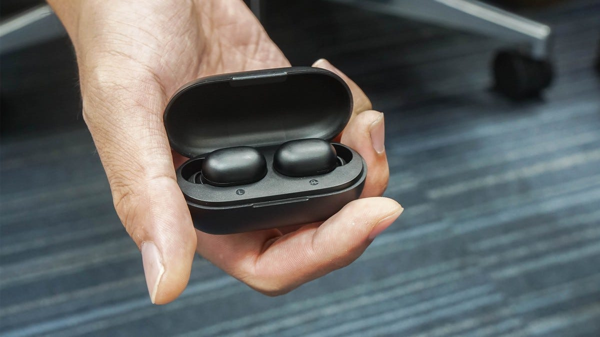 A man's hand holding a set of wireless earbuds in their case.