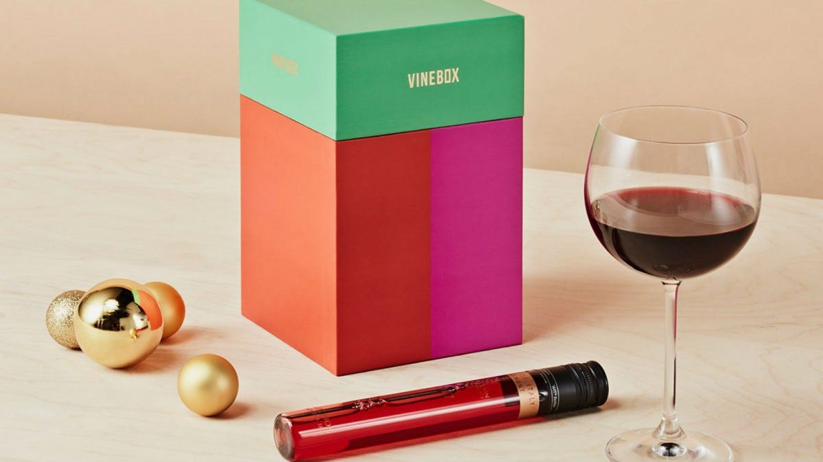 A Vinebox next to some Christmas ornaments, a glass of wine, and a vial filled with a sample of wine.