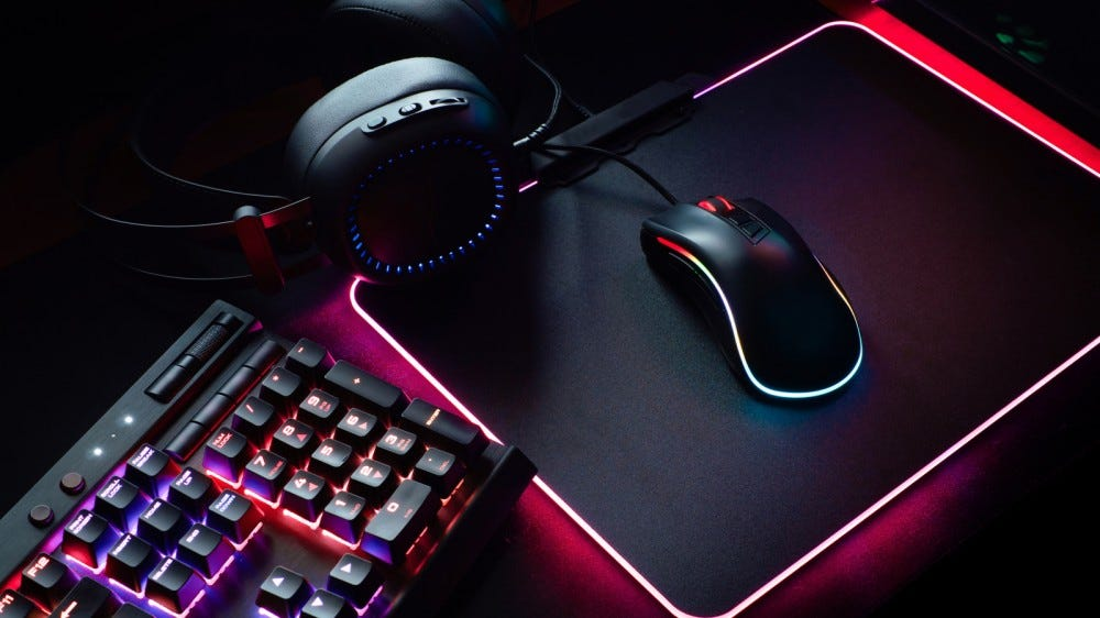 Gaming keyboard, headset, and mouse arranged on a desk