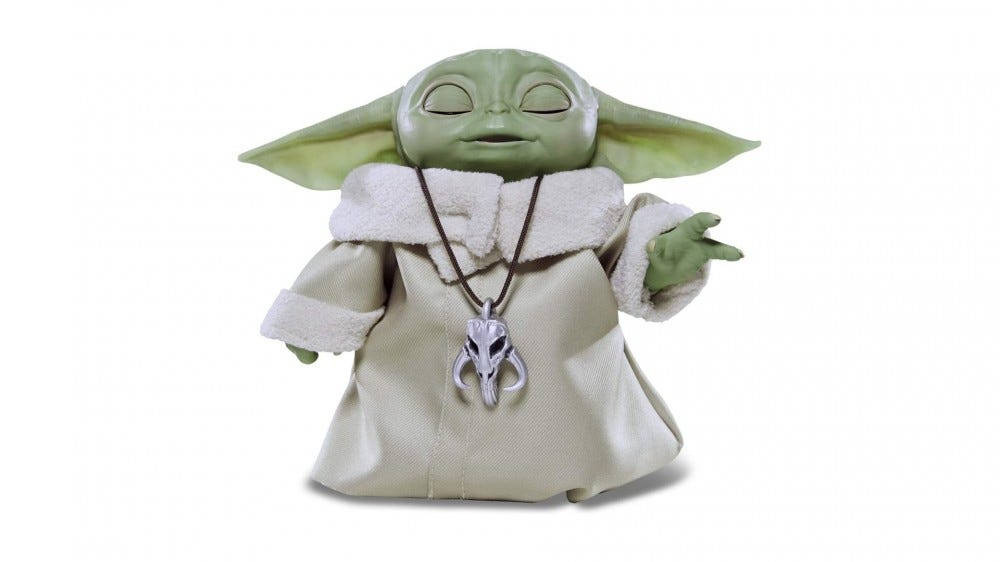 An animatronic Baby Yoda with eyes closed and had lifted, as though using the Force.