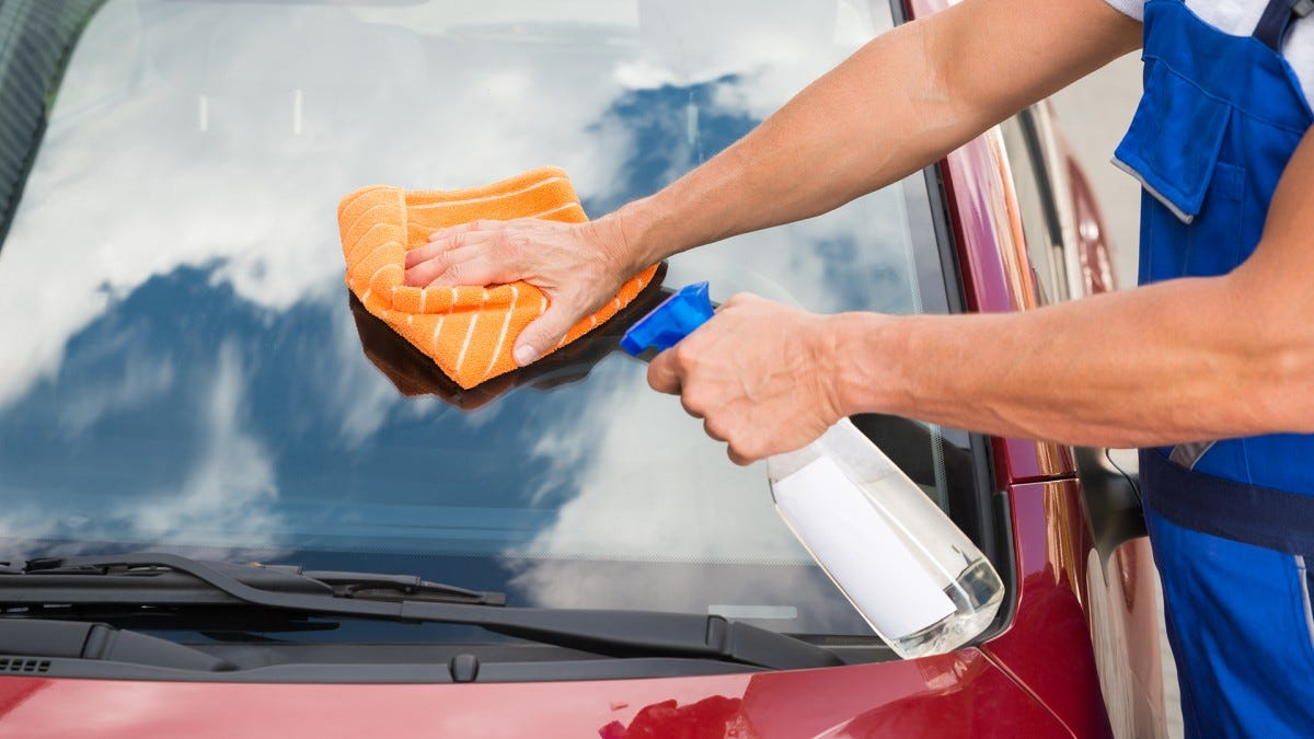 A man cleaning a car's windshield.
