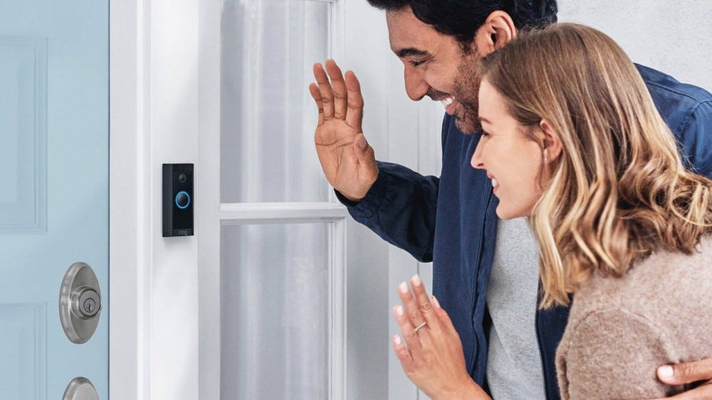 Two people wave to a small Ring Doorbell