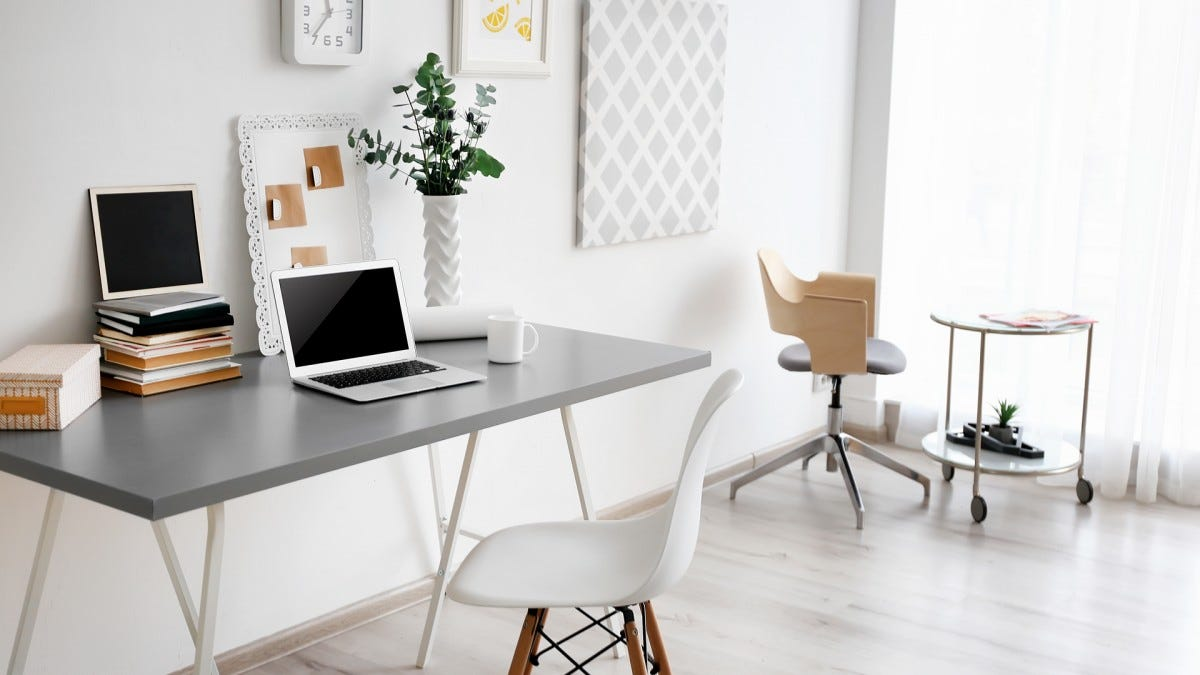 A clean, mostly-white workspace with a laptop on a desk