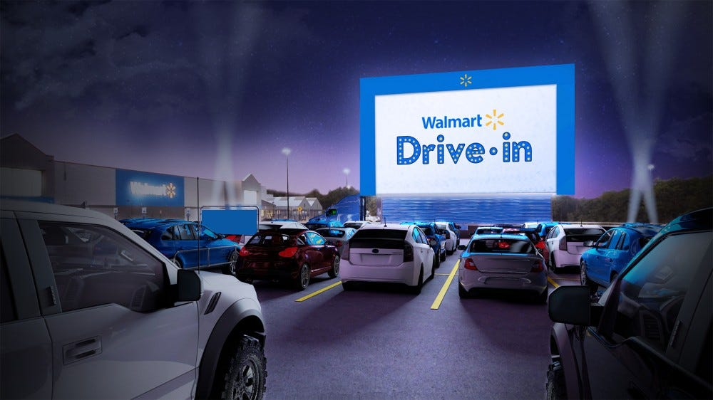 A Walmart parking lot with a large theater screen.