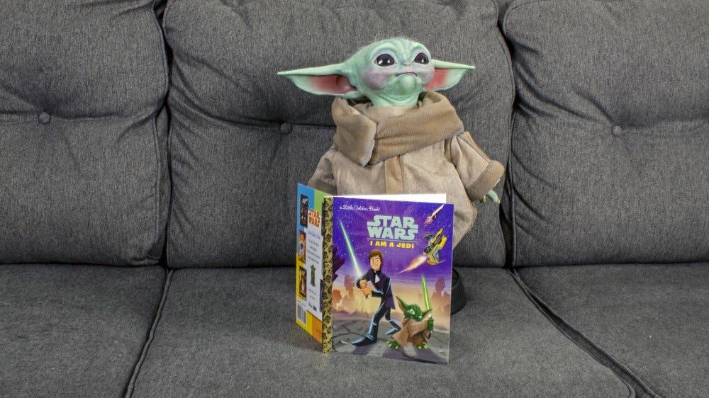 Baby Yoda next to a child's 'Star Wars' book.