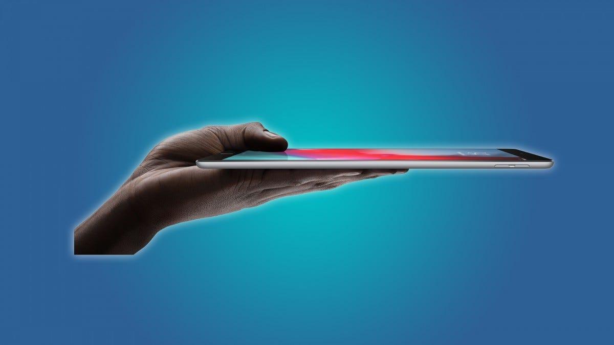A hand holding an iPad