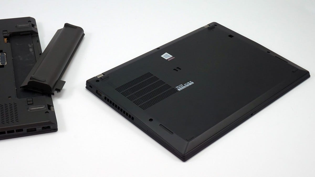 The back of a Lenovo T450s with its 3-cell battery and the T490s sitting next to it.
