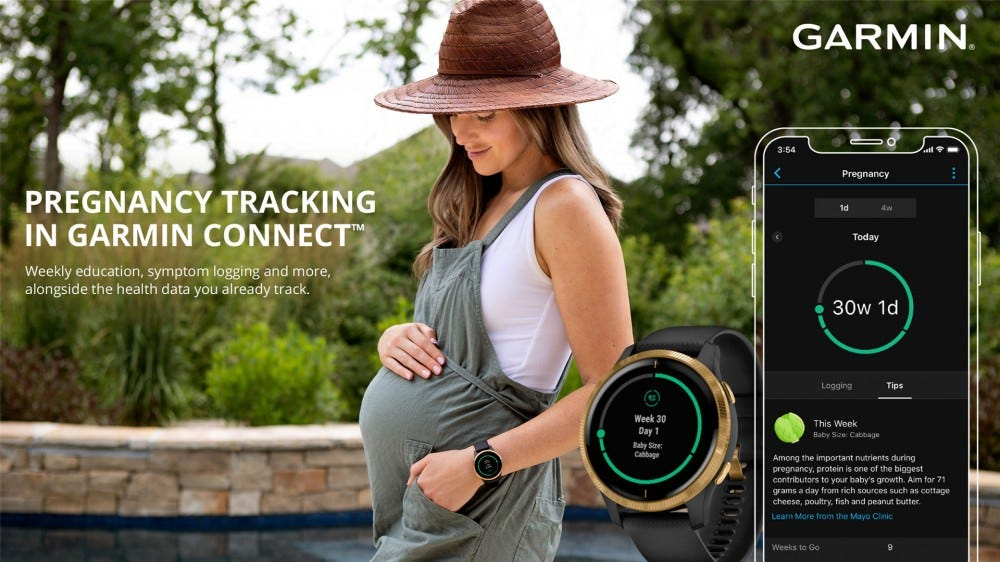 A woman holder her pregnant belly while wearing, uh, a romper? Jumper? I'm not sure what it is. A Garmin watch and the Connect app are off to the side showing the new pregnancy tracking features