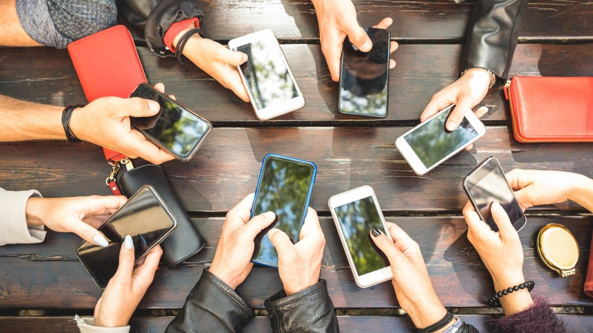 A bunch of hands in a circle holding phones.