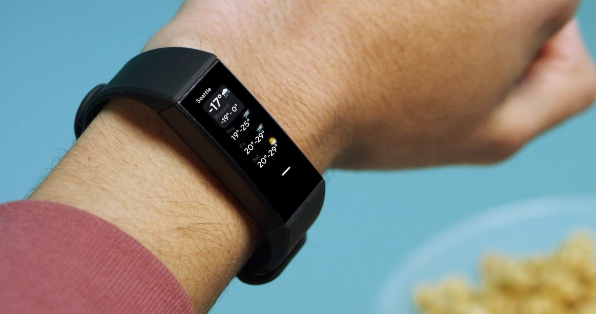 A fitbit inspire 2 on someone's wrist, shows outside