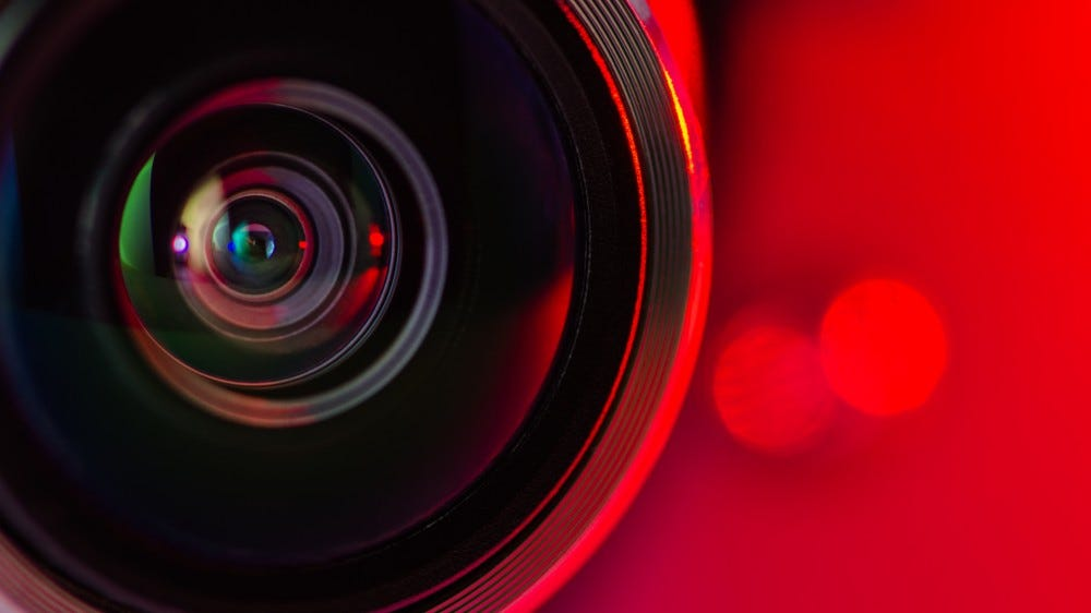 A security camera lens with a red background and slight bokeh