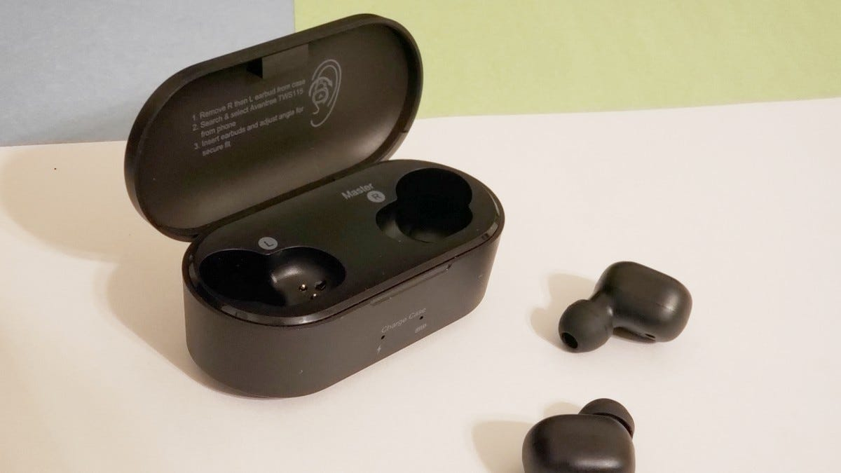 The Avantree TWS115 True Wireless Earbuds sitting on a table next to their case.