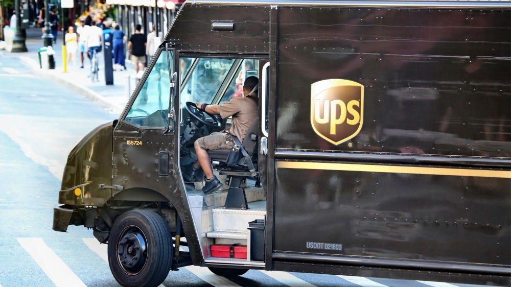 Egy utcán kanyarodó UPS teherautó.