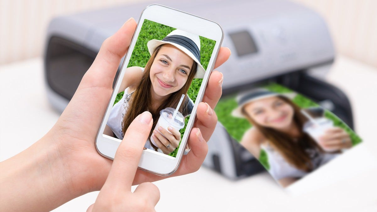 A woman printing out selfies from a photo printer.