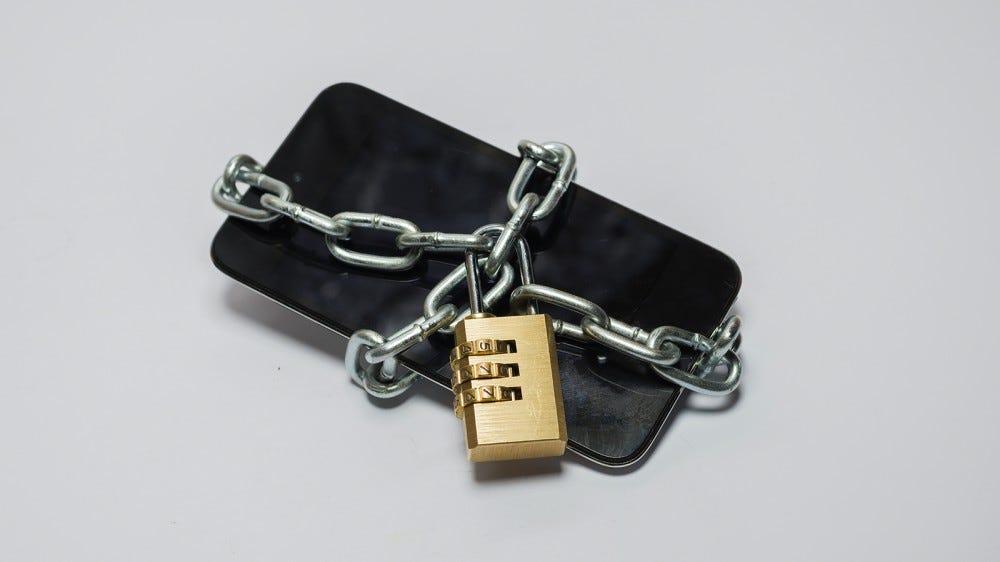 Láncba csomagolt mobiltelefon lakattal.