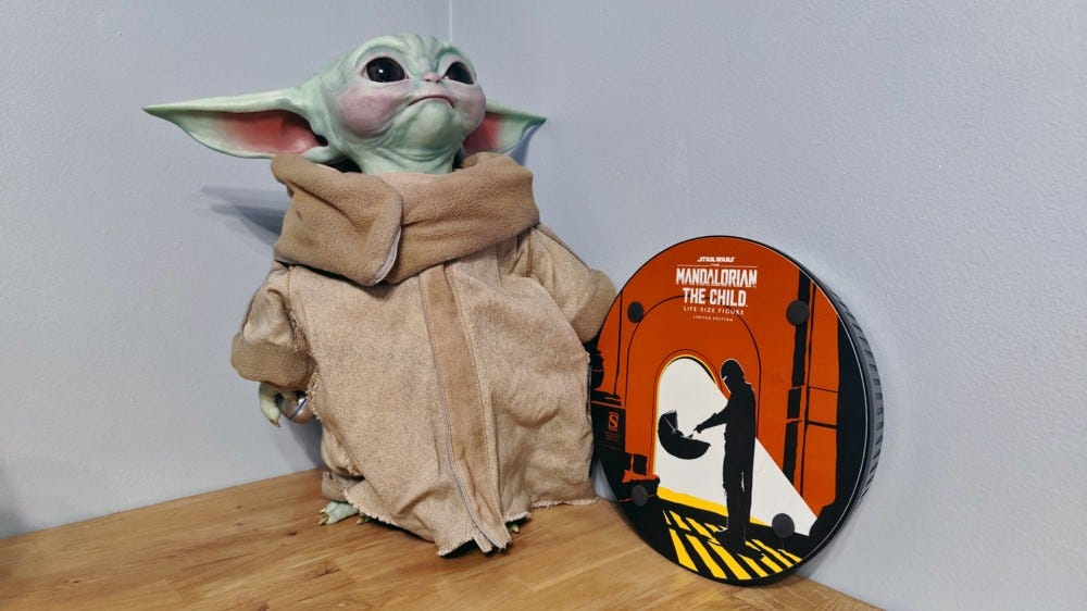 The bottom of a stand, showing stylized artwork of The Mandalorian finding Baby Yoda